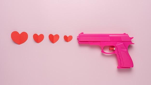 Creatieve achtergrond gemaakt met roze pistool en rode papieren harten
