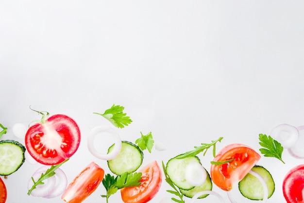 Creatieve achtergrond, lay-out, concept vers gezond dieet van salade, van de peterselieuien van verse rauwe groententomaten de komkommergreens, eenvoudig patroon