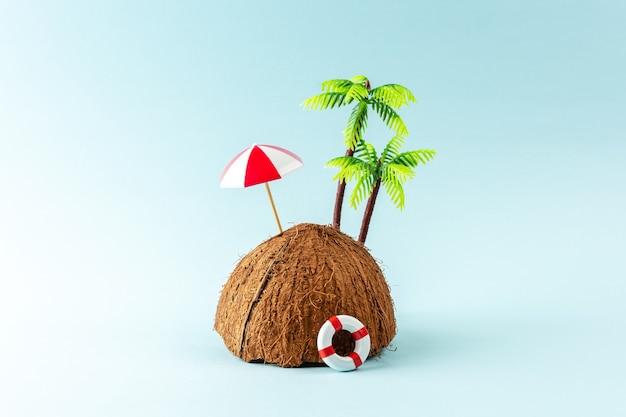 Creatieve achtergrond met kokosfruit en palmboom op pastelblauwe achtergrond