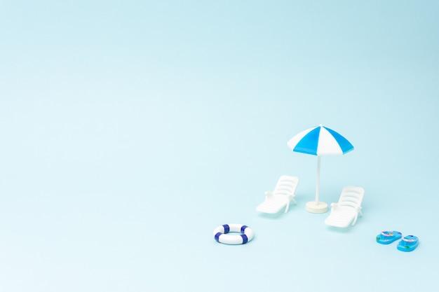 Creatieve achtergrond met ligbedden en parasol op pastelblauwe achtergrond