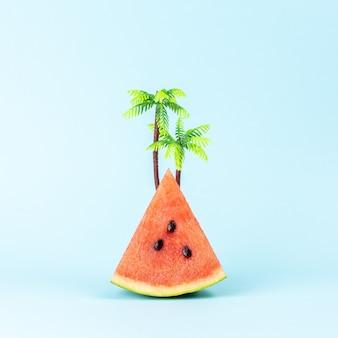 Creatieve achtergrond met watermeloen en palmboom op pastelblauwe achtergrond