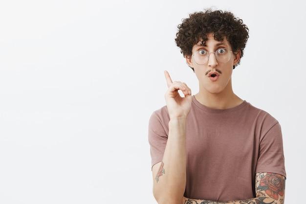 Creatieve advertentie slimme jongeman met snor krullend donker haar en getatoeëerde arm wijsvinger opheffen in eureka gebaar hijgend een geweldig idee ontdekken of een geniaal plan uitvinden suggestie toevoegen