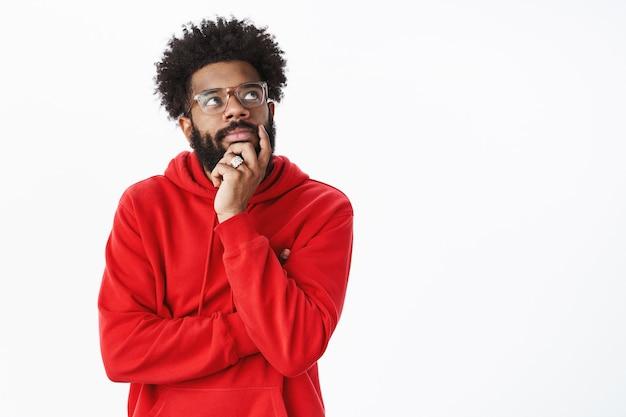 Creatieve afro-amerikaanse bebaarde man met afro-kapsel in bril en rode hoodie die een nieuw lied maakt, staande in een doordachte pose die de kin aanraakt en er dromerig uitziet, gefocust op de rechterbovenhoek, denkend