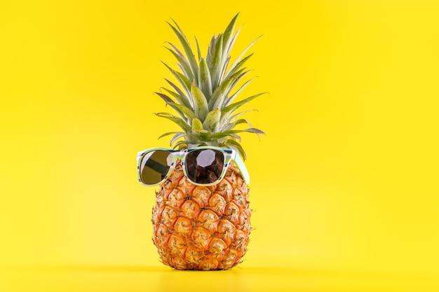Creatieve ananas met zonnebril geïsoleerd op gele achtergrond, zomervakantie strand idee ontwerppatroon, kopie ruimte, close-up, blanco voor tekst