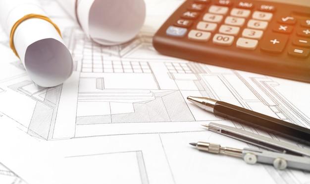 Creatieve architect die achtergrond projecteert, kantoortafel met rekenmachine, gereedschap voor apparatuurarchitect en schetsblauwdrukken, kopieer ruimtefoto