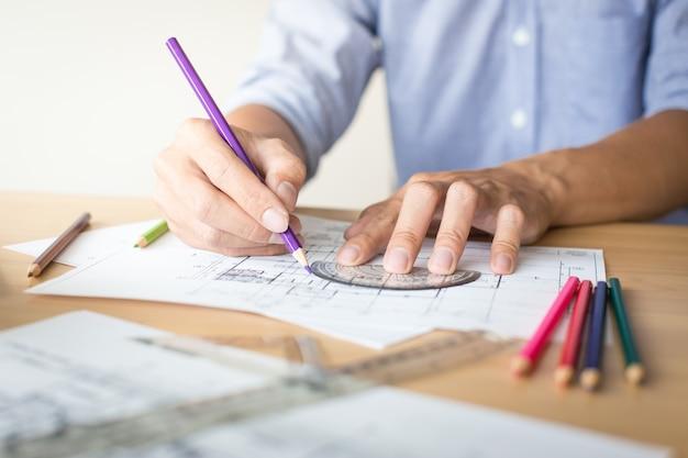 Creatieve architect die op de grote tekeningen uitsteekt in het donkere kantoor of café met donkere en retro stijl.
