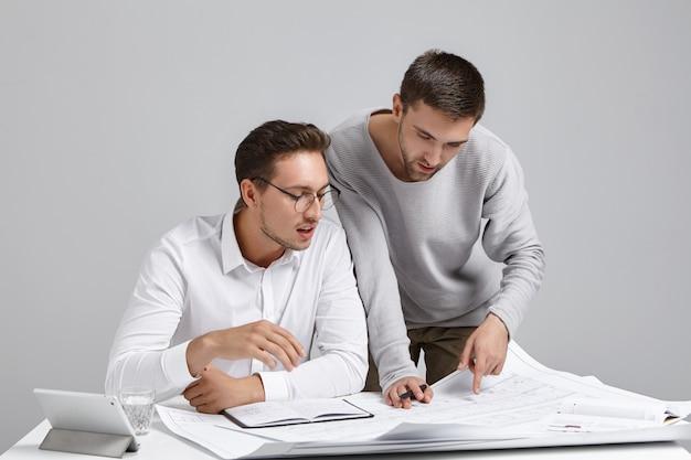 Creatieve architecten ontwikkelen huisplan, kijken aandachtig naar blauwdrukken, bestuderen tekeningen,