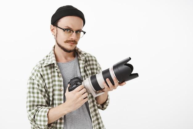 Creatieve artistieke knappe volwassen mannelijke fotograaf in zwarte hipster muts en transparante bril met professionele camera en staren met belangstelling naar voren om foto's te maken