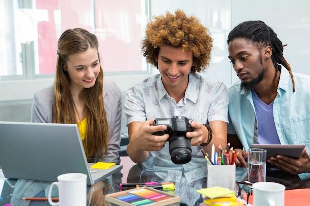 Creatieve bedrijfsmensen die digitale camera bij bureau bekijken