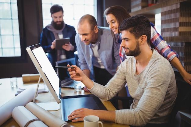 Creatieve bedrijfsmensen die over computer bespreken