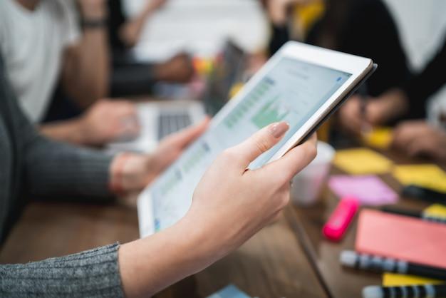 Creatieve bedrijfspersoon die aan digitale tablet werkt en wat informatio op de werkvloer cheking. technologie concept.