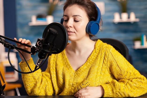 Creatieve beïnvloeder met koptelefoon die zich voorbereidt om te spreken tijdens live op sociale media die videovlog opneemt