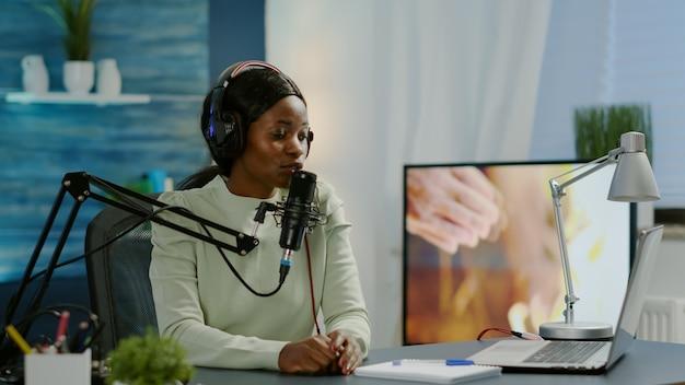 Creatieve beïnvloeder met koptelefoon klaar om te spreken tijdens live op sociale media die videovlog opneemt. on-air online productie internet uitzending show host streaming podcast inhoud van studio