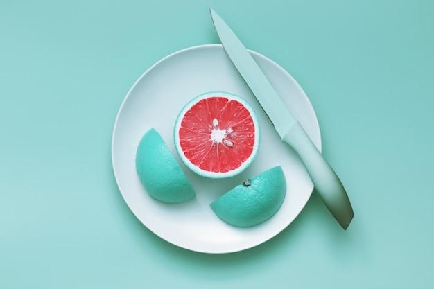 Creatieve blauwe grapefruitplakken die op plaat met mes worden gesneden