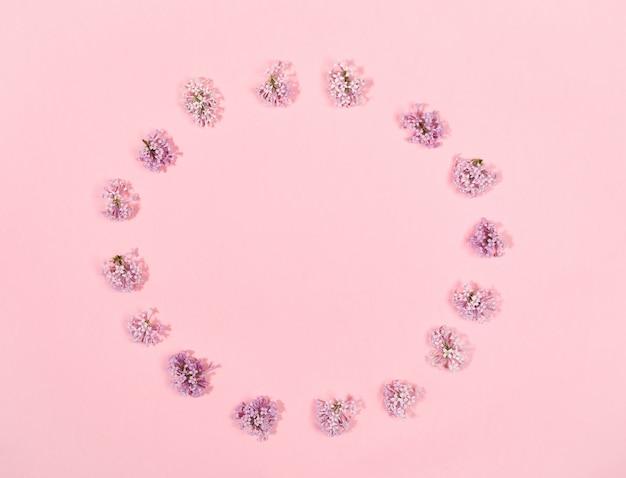Creatieve bloemen minimale achtergrond met bloemen van lila neergelegd in cirkel op trendy roze achtergrond. bovenaanzicht.