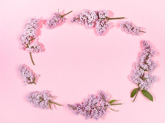 Creatieve bloemen voorjaar achtergrond met twijgen van lila aangelegd in ovaal met kopie ruimte erin op trendy roze achtergrond.