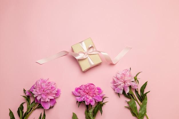 Creatieve bloemensamenstelling van pioenen en gift op wit en roze