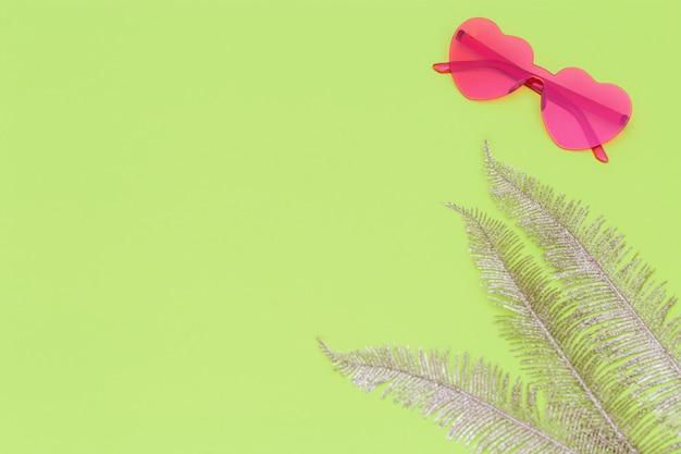 Creatieve bovenaanzicht met moderne zonnebril op groenboek achtergrond. hartvormige bril pastelkleurig. creatief zomerconcept. plat lag met kopie ruimte.