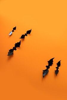 Creatieve bovenaanzicht plat lag herfst halloween compositie van zwarte papieren vleermuizen vliegen omhoog op een oranje achtergrond