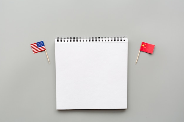 Creatieve bovenaanzicht plat leggen van de vs en china vlaggen, mockup en kopie ruimte op grijs