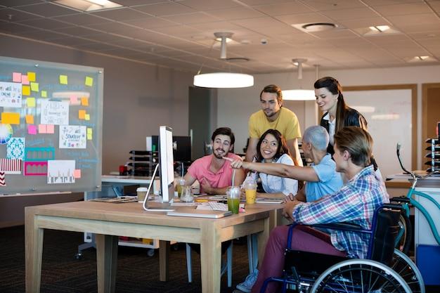 Creatieve business team bespreken tijdens het samenwerken op desktop pc op kantoor