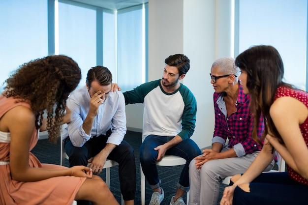 Creatieve business team troostende boos collega op kantoor