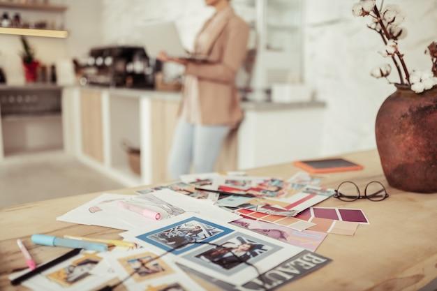 Creatieve chaos. vrouw met een laptop die achter de tafel staat vol met verschillende modefoto's en schetsen.