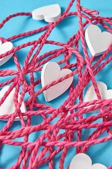 Creatieve close-up lay-out van rood verward touw en kleine wit geschilderde houten harten