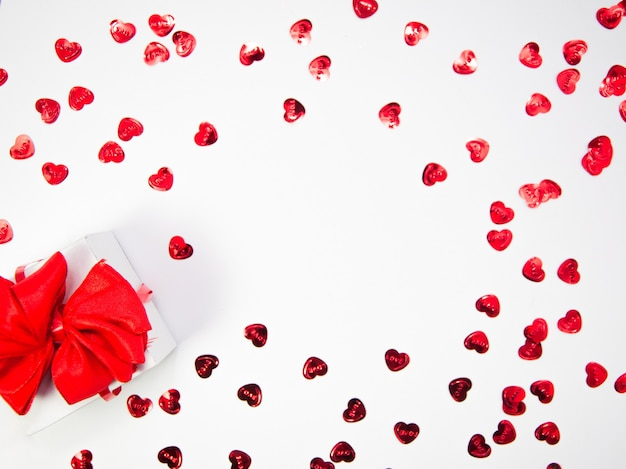 Creatieve compositie gemaakt van harten en witte geschenkdoos met rood lint op witte achtergrond met kopie ruimte, gelukkige valentijnsdag, moederdag, plat lag, bovenaanzicht