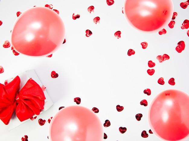 Creatieve compositie gemaakt van hartjes en witte geschenkdoos met rood lint en ballonnen op witte achtergrond met kopie ruimte, happy valentijnsdag, moederdag, plat lag, bovenaanzicht