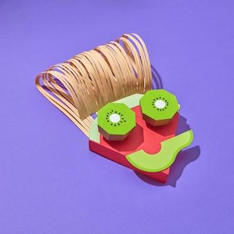 Creatieve compositie in de vorm van het gezicht van de jongen, handgemaakt van kleurrijk papier uit delen van papercraft fruit op een paarse achtergrond met schaduwen, kopieer ruimte. vegetarisch concept.