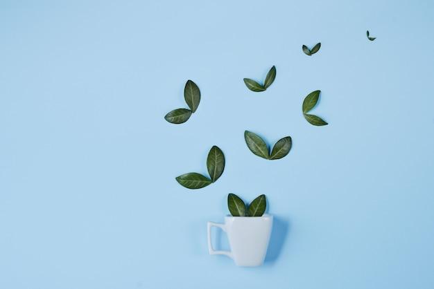 Creatieve compositie. koffiekopje met vogels gemaakt van natuurlijke groene bladeren op blauwe achtergrond