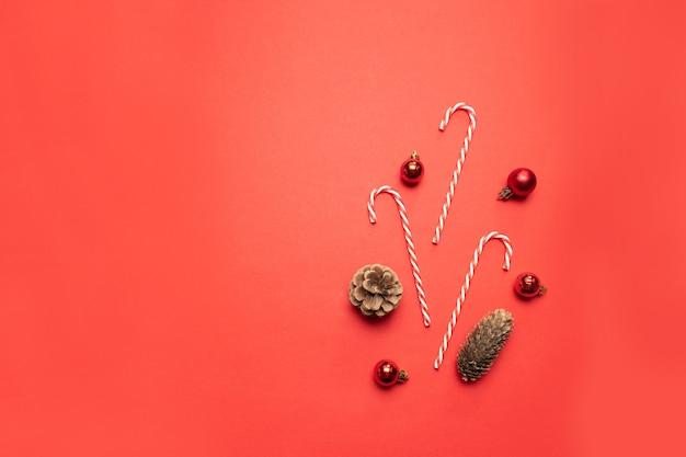 Creatieve compositie met dennenappels, rode ballen en snoepriet op een rode achtergrond bovenaanzicht. platte compositie voor kerstmis of nieuwjaar