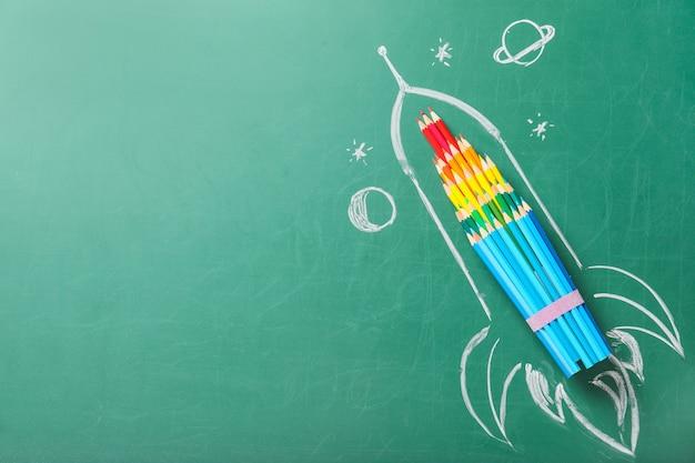 Creatieve compositie met getekende ruimteraket en briefpapier op schoolbord