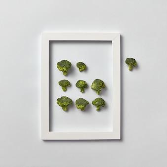 Creatieve compositie met vers geplukte groene broccoli in een frame en een deel eruit op een lichtgrijze muur, plaats voor tekst. plat leggen. veganistisch concept.