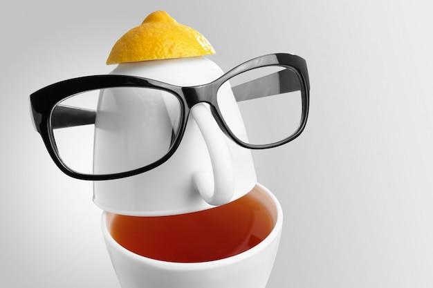 Creatieve compositie rond het thema thee. theekopjes in de vorm van een menselijk gezicht met een bril