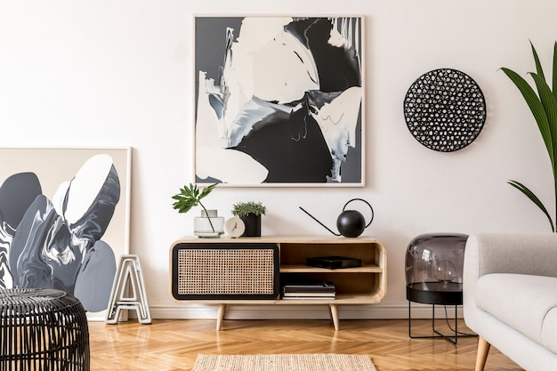 Creatieve compositie van een gezellig en stijlvol woonkamerinterieur met frame, houten commode, bank en accessoires. witte muren en parketvloer. neutrale kleuren.