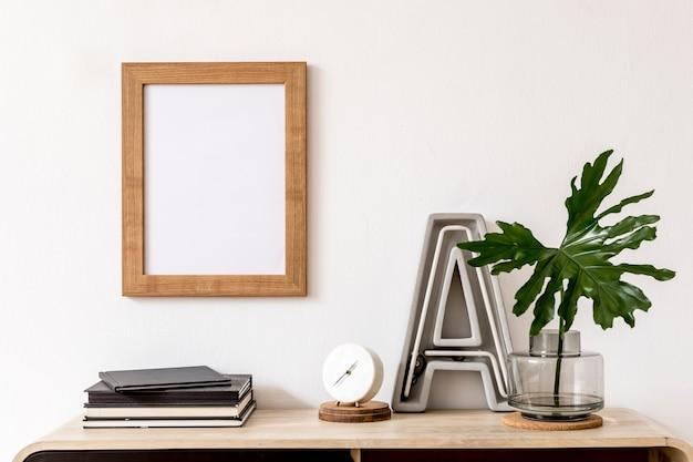 Creatieve compositie van een gezellig en stijlvol woonkamerinterieur met frame, houten commode en accessoires. witte muren. minimalistisch concept. neutrale kleuren.