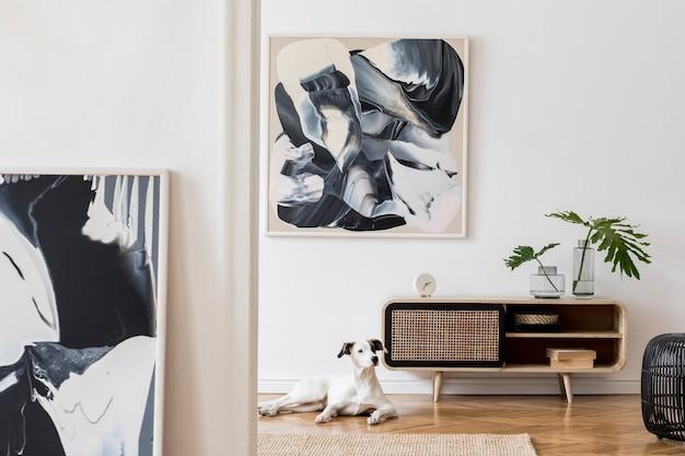 Creatieve compositie van een gezellig en stijlvol woonkamerinterieur met frame, houten commode, hond, bank en accessoires. witte muren en parketvloer. neutrale kleuren.