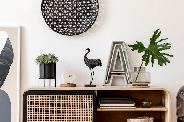 Creatieve compositie van een gezellig en stijlvol woonkamerinterieur met posterframe, houten commode, planten en accessoires. witte muren. minimalistisch concept. neutrale kleuren.
