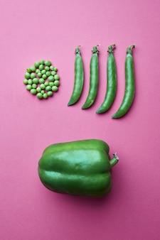 Creatieve compositie van erwtenkorrels in de vorm van een cirkel en vol gesloten peulen en groene paprika op een roze achtergrond. plat leggen. voedsel concept.