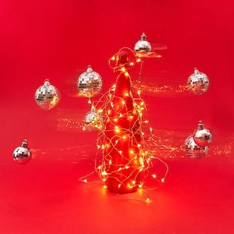 Creatieve compositie van geschilderde champagnefles bedekt met kerstslinger met glanzende lichten en glitterballen die rondzweven met paden op een rode achtergrond, kopieer ruimte. nieuwjaar wenskaart.