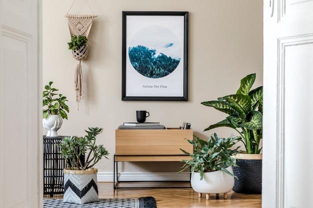 Creatieve compositie van gezellig en creatief zaalinterieur met zwart frame, houten commode en accessoires.