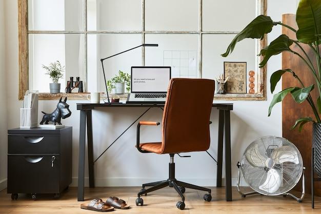 Creatieve compositie van modern mannelijk thuiskantoorinterieur met zwart industrieel bureau, bruine leren fauteuil, laptop en stijlvolle persoonlijke accessoires. sjabloon.