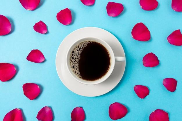 Creatieve compositie van rode rozenblaadjes en kopje koffie op blauwe achtergrond.