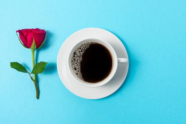 Creatieve compositie van rood roze bloem en kopje koffie op blauwe achtergrond.