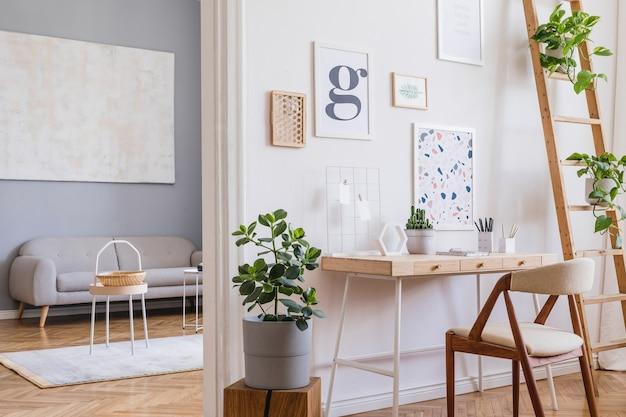 Creatieve compositie van stijlvol scandi-huiskantoorinterieur met mock-up posterframes, houten bureau, stoel, planten en accessoires. neutrale wanden, parketvloer. sjabloon.