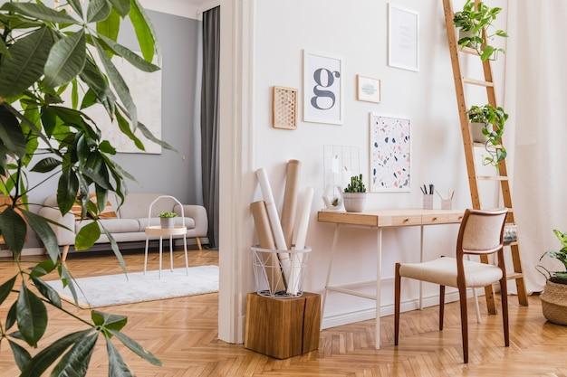 Creatieve compositie van stijlvol scandinavisch kantoor aan huis interieur met posterframes, houten bureau, stoel, planten en accessoires. neutrale wanden, parketvloer.