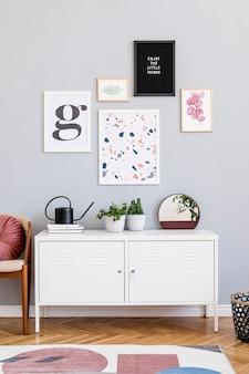 Creatieve compositie van stijlvol woonkamer modern interieur met posterframes houten commode stoel kussen spiegel planten en accessoires. neutrale wanden parketvloer