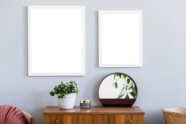 Creatieve compositie van stijlvol zaalinterieur met twee posterlijsten, houten commode, plant, spiegel en accessoires. hipster appartement concept, retro elementen.